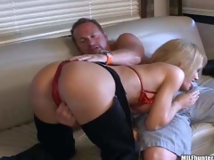 Busty mature blonde momma with big boobs in sexy cowgirl pants and red bikini enjoys in teasing her lover and giving head on the couch in front of the cam