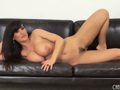 Lisa Ann gets on the floor to toy and back on the couch to pose