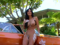 Incredibly fuckable brunette milf Phoenix Marie is washing a car completely naked and in the process her wobblers and arse get all soaped up, looking just awesome.