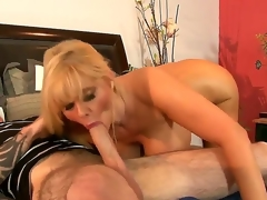Experienced seductive mature golden-haired milf Karen Fisher with big juicy booty and massive hanging hooters gives head to younger tattooed chap and rides on his huge hard boner on bed