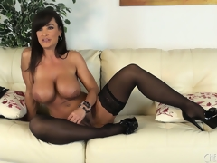 Lisa Ann positions seductively in a pair of stockings and high heels