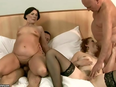 Margo T and Eodit are two sexually excited grannies that get their mouths and dripping wet pussies fucked side by side. Two fuck hungry oldies do it on a king size ottoman in steamy foursome action!